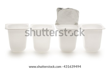 Empty crushed plastic yogurt pots on white