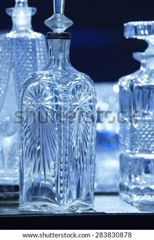 Empty crystal bottles for liquor in blue tone. Vertical