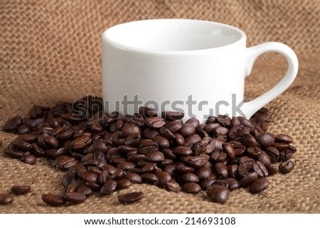 empty cup and roasted coffee beans on sackcloth - stock photo