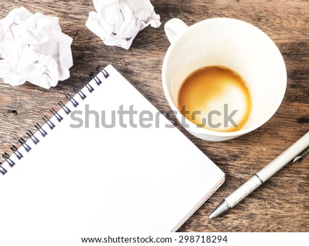 Empty cup of coffee , notepad and crumpled paper on wooden table - stock photo
