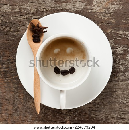 Empty cup of espresso coffee with smiling coffee beans on the table, Artistic selective focus - stock photo