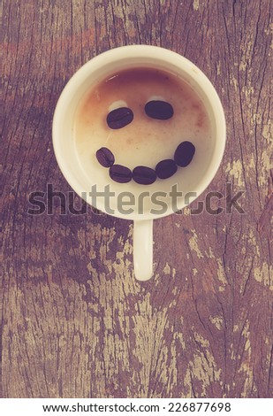 Empty cup of espresso coffee with smiling coffee beans on the table, Artistic selective focus, retro filter effect - stock photo