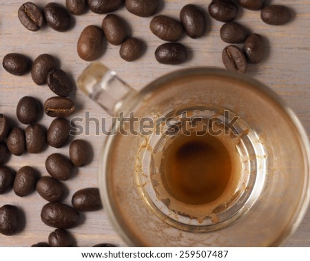 Empty Cup of hot espresso coffee and coffee crop on wood board
