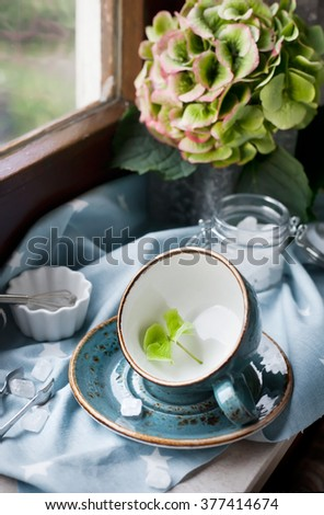 Empty cup on the attic window set with flowers, vintage style photo. Preparing breakfast in the morning, summer lunch theme, country lifestyle living concept. - stock photo