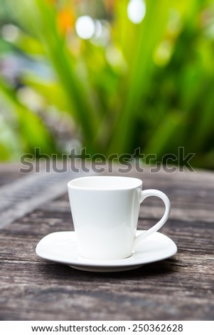 Empty cup on wood table with green nature background