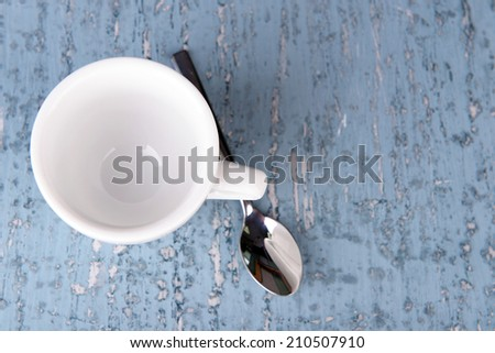 Empty cup with tea spoon on wooden background - stock photo