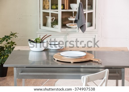 empty cutting board behind kitchen cupboard with metal kitchen countertop modern kitchen - stock photo