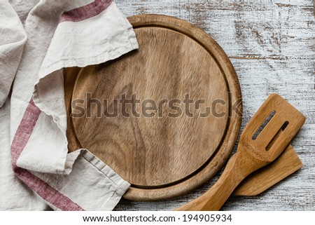 Empty cutting board on kitchen table - stock photo