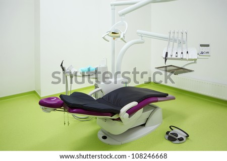 Empty dental clinic. Big and comfortable chair for patient and drill for dentist. - stock photo