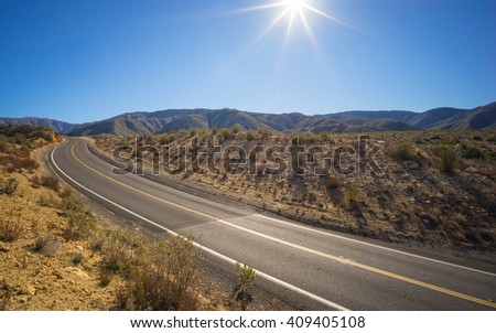 Empty desert highway through the vast Mojave of southern California. - stock photo