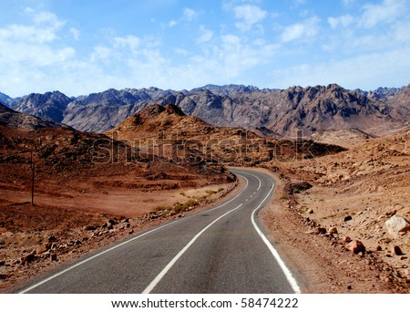 empty desert road with mountain and blue sky