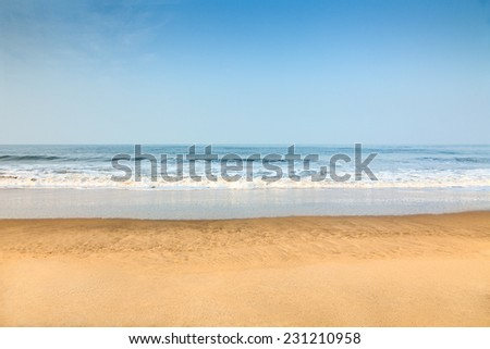 Empty deserted beach with clean blue sky - stock photo