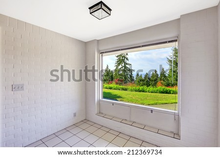 Empty dining room with beautiful window view. Tile floor and painted white brick walls. Build in 1952. Unique old modern home.