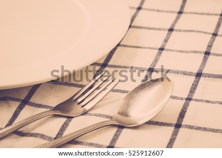 Empty dinne plate and fork and spoon. vintage filter
