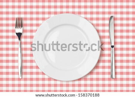 empty dinner plate top view on pink picnic table cloth - stock photo