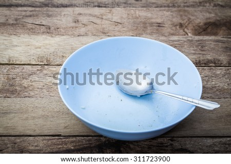 Empty dish after eat food on the wooden table - stock photo