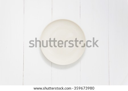 Empty dish on wooden white table, Top view - stock photo
