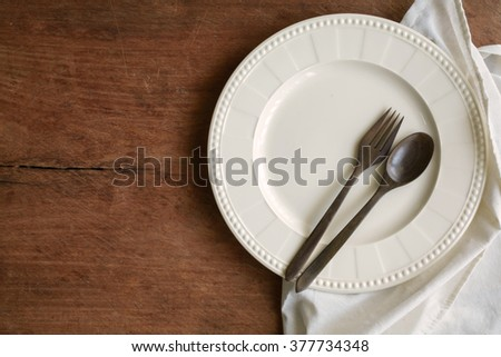 Empty dish with wooden spoon and fork on old wooden background, Top view - stock photo