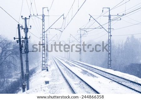 Empty electric railroad in winter forest  - stock photo