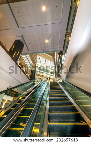 Empty escalator stairs.  Fragment of the architecture of modern lobby, hallway of the luxury hotel, shopping mall, business center in Vancouver, Canada. Interior design. - stock photo