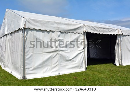 Empty event tent in a fair outdoor on green grass under blue sky. concept - stock photo