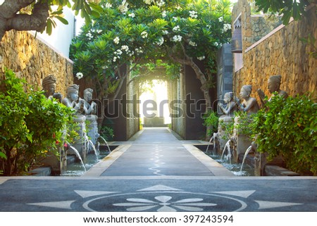 empty exotic background with tropical plants, flowers, sculptures and arched passage - stock photo