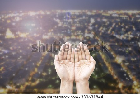 Empty female open human hands prayer with abstract Background top view of Paris in lights and bokeh. Concept for pray for usa, Christmas, Forgiveness. World Environment Day CSR Orlando shooting ISIS  - stock photo