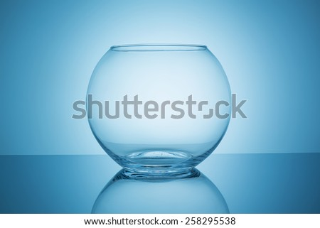 empty fishbowl glass on blue background - stock photo