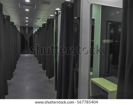 Empty fitting room in an fashion store with mirrors and black curtains