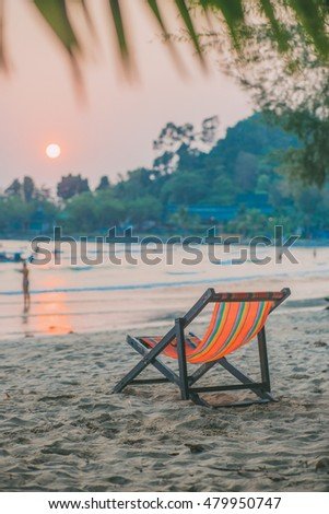 Empty folding lounge chair on the sand beach. Sunset eunrise time. Soft shadows. Vacation wallpaper. Travel inspiration. Postcard concept. Vintage effect.