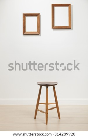 empty frames and chair on a white wall, interior