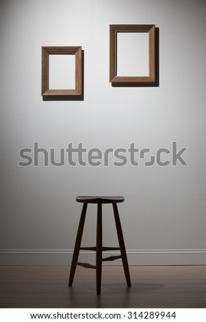 empty frames and chair on a white wall, interior - stock photo