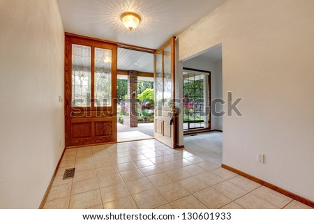 Empty front entrance with open door. Home interior with white walls.