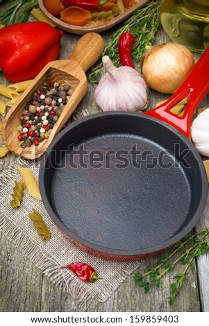 empty frying pan, vegetables and spices on wooden background, top view, vertical