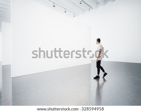 Empty gallery interior with white canvas and man.  - stock photo