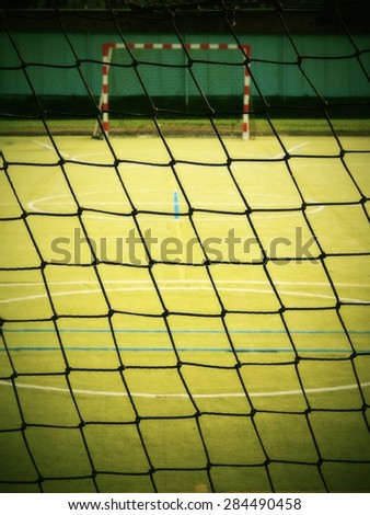 Empty gate in playground. Outdoor football or handball playground, plastic light green surface on ground - stock photo