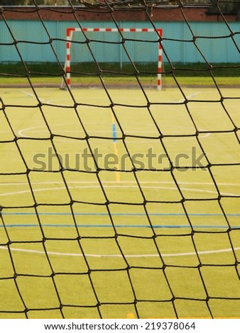 Empty gate. Outdoor football or handball playground, plastic light green surface on ground - stock photo