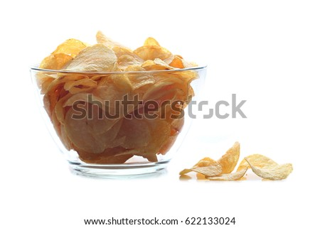 Empty glass and bottle of beer with crumbs of chips on wooden table