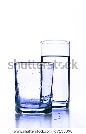 Empty glass before full glass of fresh water.