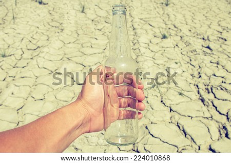 Empty glass bottle from under the water in a hand on a background of the desert - stock photo