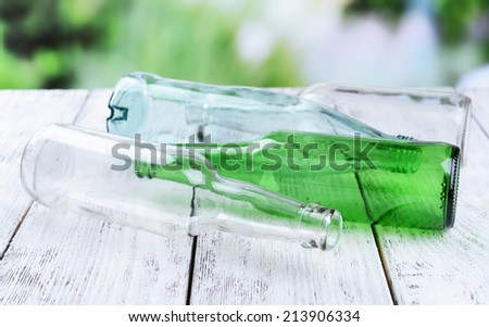 Empty glass bottles on table on bright background - stock photo