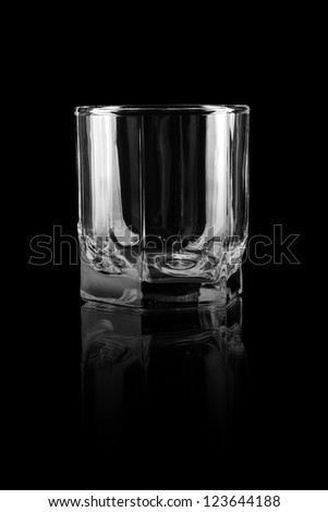Empty glass for whiskey on a reflective surface on black background - stock photo