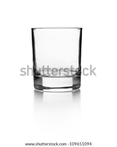 Empty glass for whiskey on a reflective surface on white background