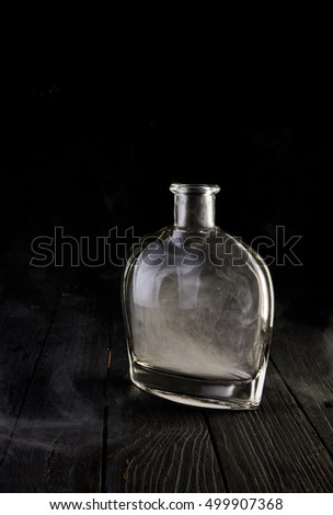 Empty glass liquid decanter graceful shape on a black wooden background with smoke in it. Crystal pitcher for alcohol in directional light. Isolated