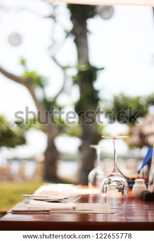 empty glass of vine on table with tree background - stock photo