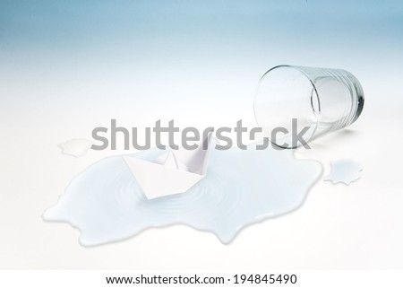 Empty glass of water with paper boat  (surreal concept)  - stock photo