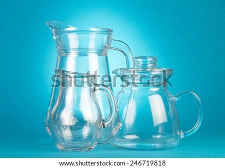 Empty glass pitchers on blue background - stock photo