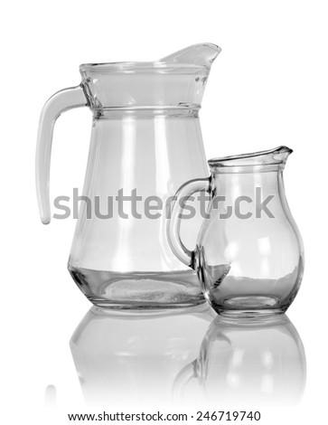 Empty glass pitchers on white background - stock photo