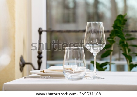 Empty glasses and plates set in restaurant - stock photo