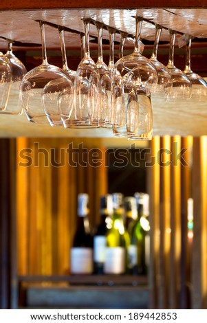 Empty glasses for alcohol beverage above a bar rack background